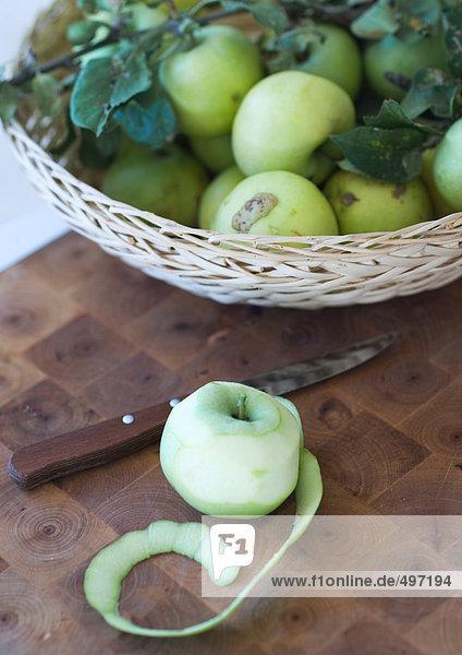 Teilweise geschälter Apfel und Apfelkorb