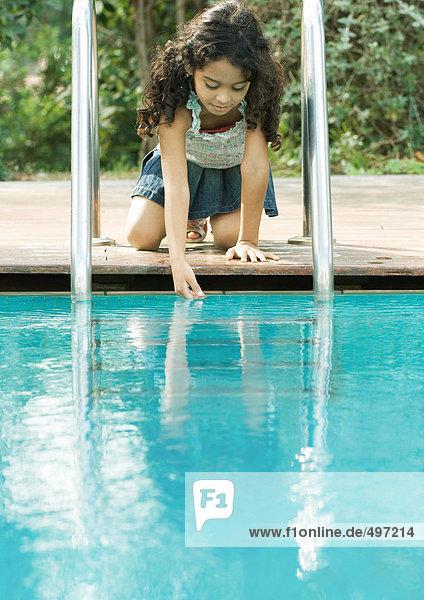 Mädchen kauernd am Beckenrand  berührende Wasseroberfläche