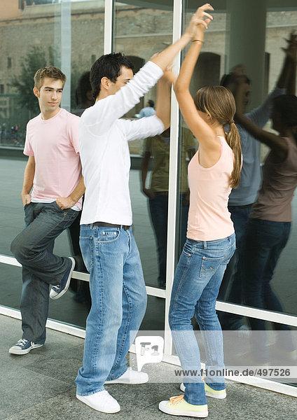 Teenager hängen herum  zwei tanzen  während ein Freund zusieht.