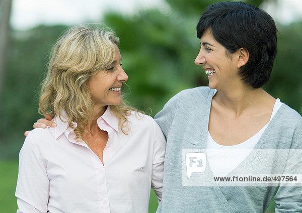 Mittlere erwachsene Frau und reife Frau lächeln sich an.