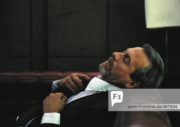 Geschäftsmann lehnt den Kopf auf den Rücken des Sofas und passt die Krawatte an.
