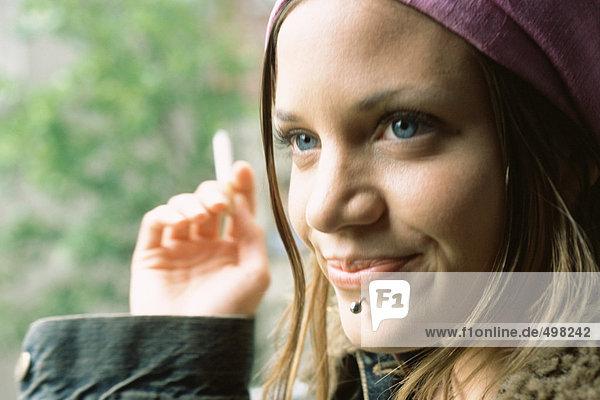 Junge Frau mit Gesichtspiercing  Rauchen  Nahaufnahme