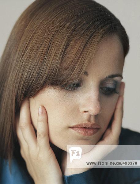Frau hält Gesicht in Händen  schaut nach unten  Porträt