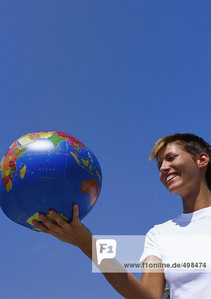 Junge Frau mit Globusball
