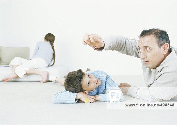 Mann und Sohn spielen mit Würfeln auf dem Boden