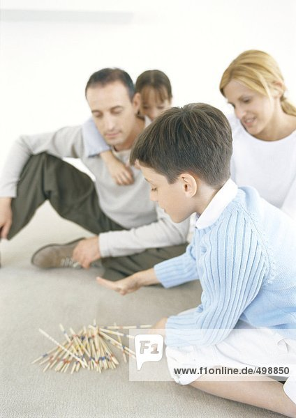 Familienspielende Pick-Up-Sticks auf dem Boden
