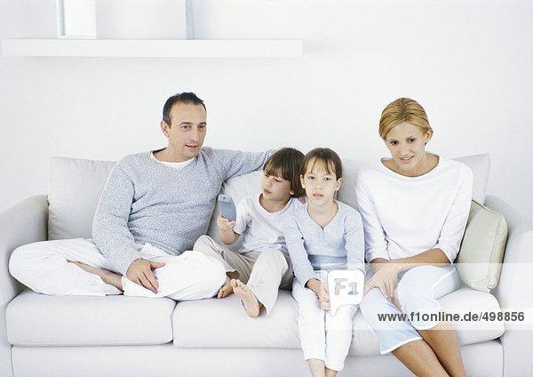 Familie sitzt zusammen auf dem Sofa