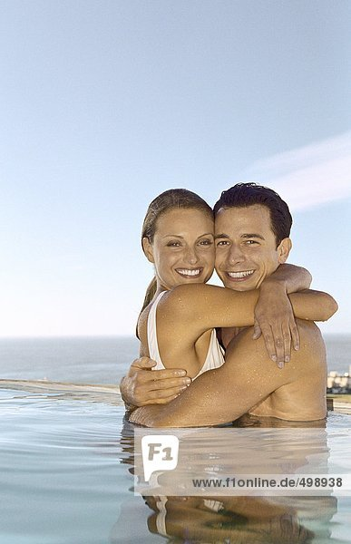 Junges Paar umarmt im Pool