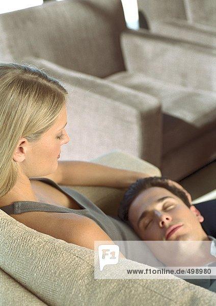 Mann schlafend mit Kopf auf dem Schoß der Frau