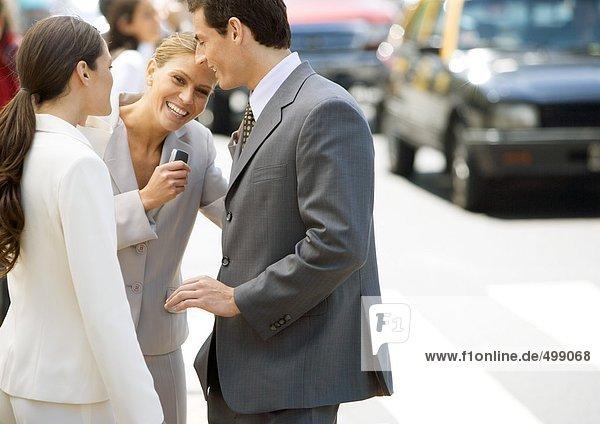 Geschäftsfreunde stehen am Straßenrand  Frau lacht