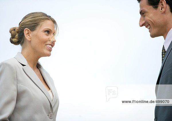 Geschäftsfrau und Geschäftsmann lächeln sich an.