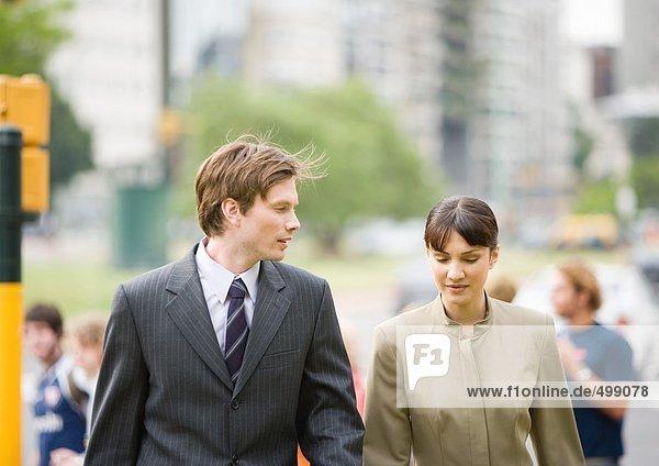 Ein junger Geschäftsmann  der mit einer Kollegin geht.