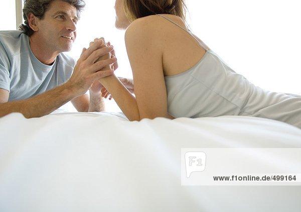 Paar auf dem Bett liegend  Händchen haltend