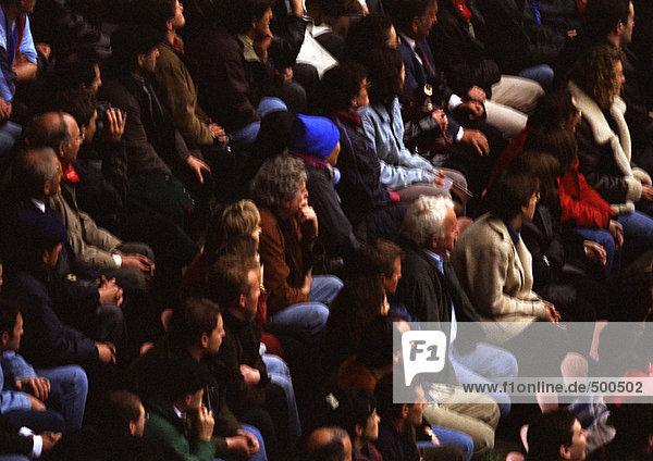 Menschenmenge sitzend  defokussiert