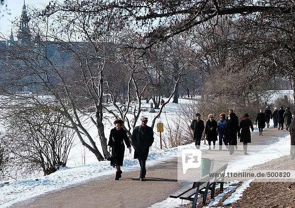 Schweden  Stockholm  Menschen  die im Park im Schnee spazieren gehen