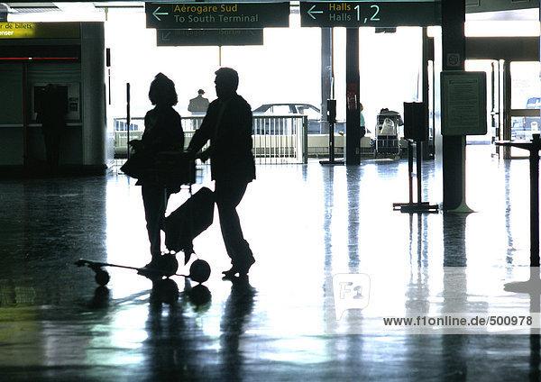 People walking in train station  silhouette.