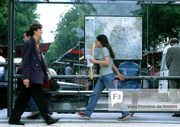Leute  die an der Bushaltestelle vorbeigehen  verschwommen.