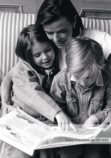Junge Frau mit zwei Kindern auf dem Schoß  Blick auf Buch  s/w