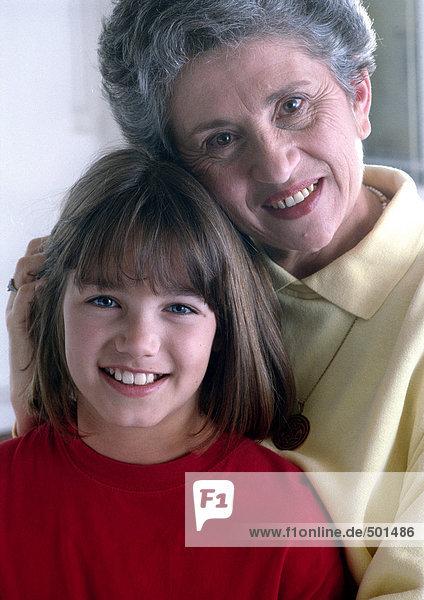 Mädchen und Seniorin vor der Kamera  lächelnd  Porträt.