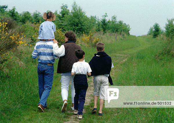 Familie beim gemeinsamen Spaziergang im Freien  Rückansicht.