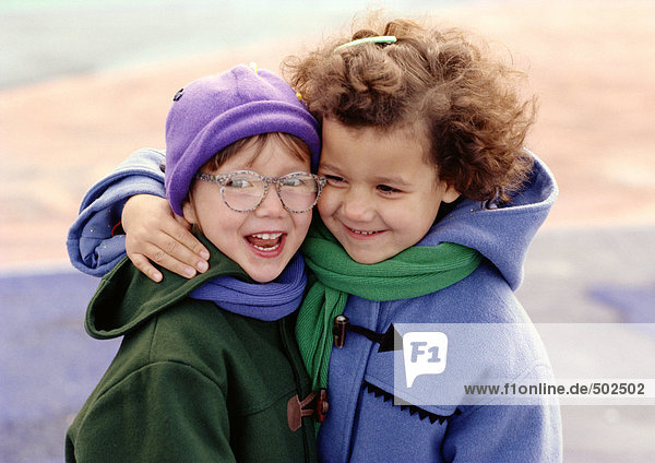 Two children hugging  smiling