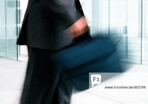 Mann mit Laptoptasche  Mittelteil  verschwommene Bewegung
