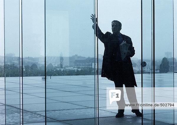 Mann steht vor Glastüren der Gebäudehallen  winkt