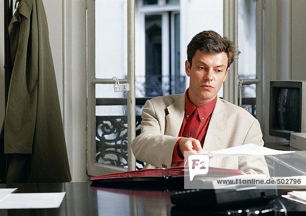 Mann am Schreibtisch sitzend  Papier haltend