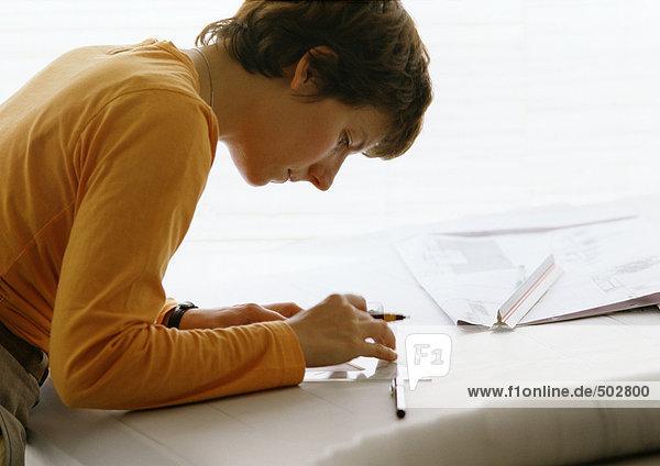 Frau beugt sich über den Tisch  hält Winkel und Stift  Seitenansicht