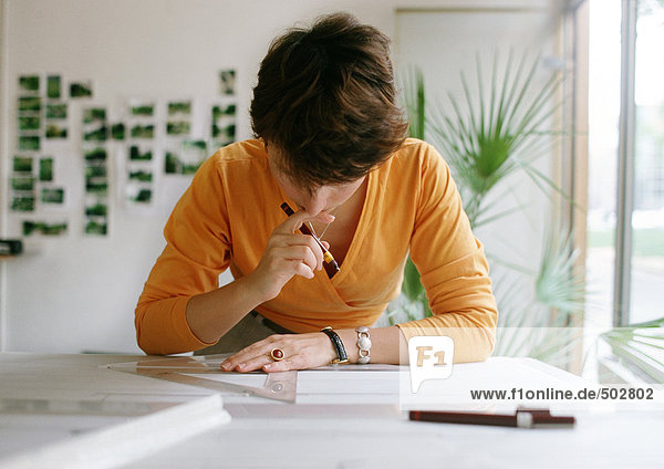 Frau beugt sich über den Tisch  hält Winkel und Kugelschreiber
