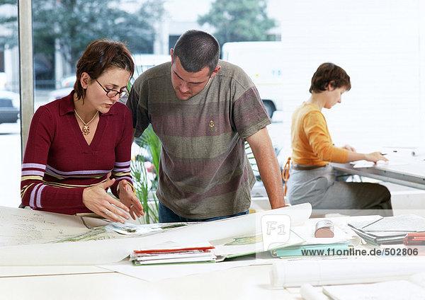 Frau und Mann beim Betrachten von Plänen  Frau im Hintergrund sitzend