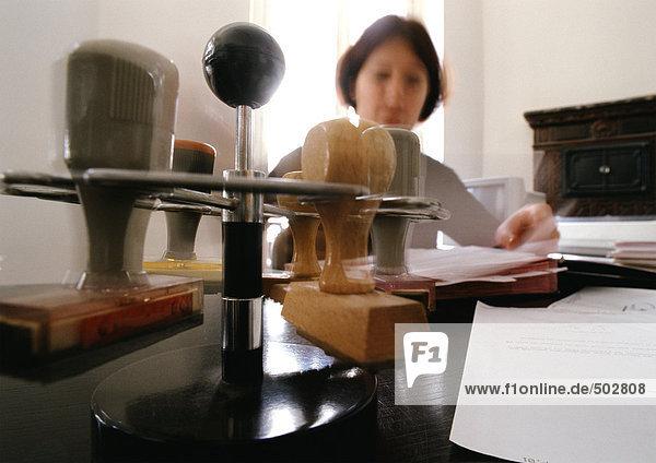 Stempel auf Gestell und Frau am Schreibtisch sitzend  verschwommen