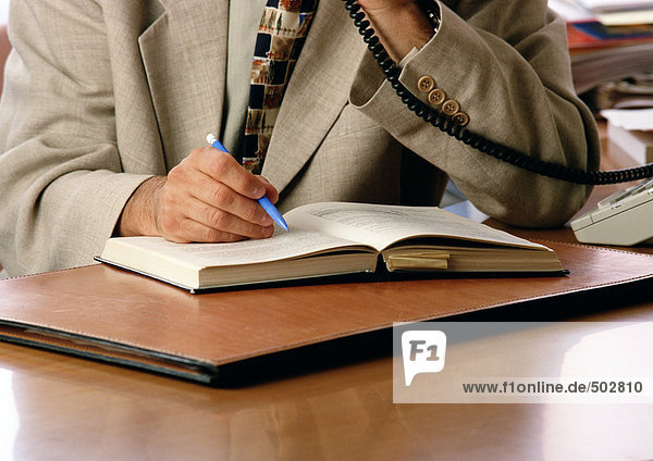 Person mit Stift und Telefon  Mittelteil