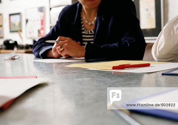 Frau am Schreibtisch sitzend  Teilansicht