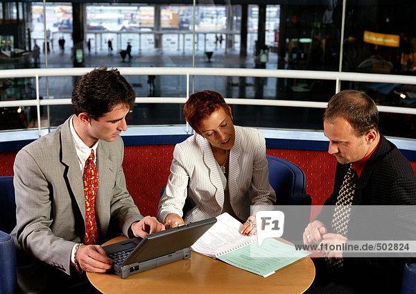 Drei Personen sitzen am Tisch  eine hält den Laptop.