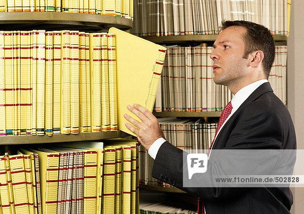 Mann nimmt Dokument aus dem Regal