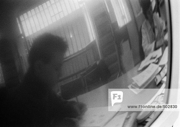 Silhouette des Mannes am Schreibtisch reflektiert im Bildschirm  s/w