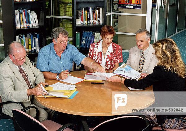 Fünf Personen sitzen im Konferenzraum