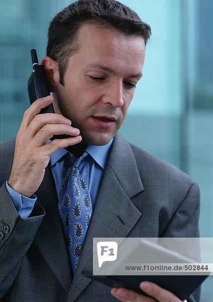 Mann mit Handy beim Betrachten des Taschencomputers  Porträt