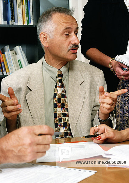 Man sitting at table  gesturing with hands