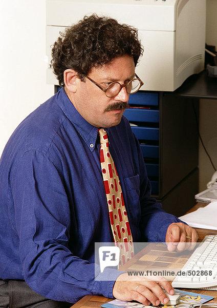 Mann am Schreibtisch sitzend  Maus haltend