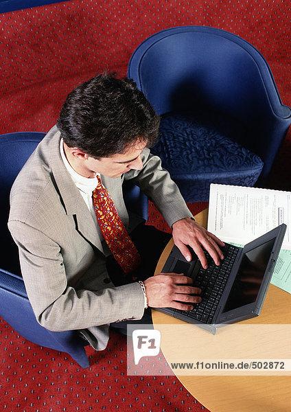 Mann am Tisch sitzend  mit Laptop-Computer  erhöhte Ansicht