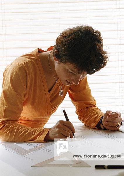 Frau beugt sich über den Tisch  hält Stift