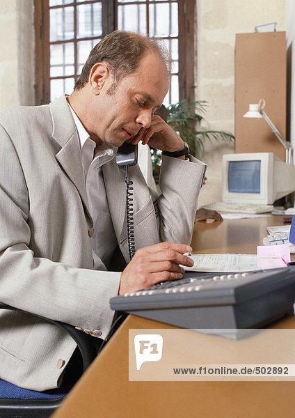 Mann am Schreibtisch sitzend  telefonierend  Seitenansicht