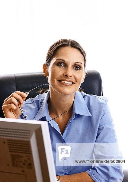 Frau am Schreibtisch sitzend  lächelnd  Portrait