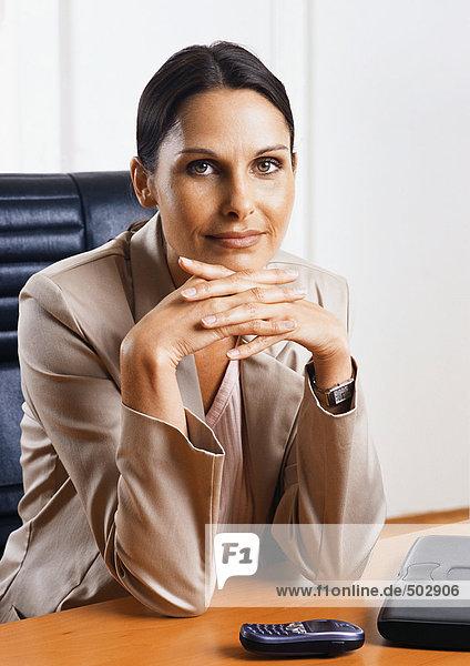 Frau sitzt am Schreibtisch  Hände zusammen  Porträt