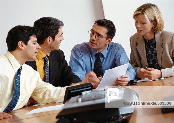 Drei Geschäftsleute und eine Geschäftsfrau  die das Dokument prüft.