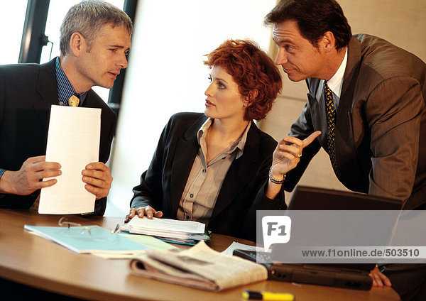 Zwei Geschäftsleute und eine Geschäftsfrau am Tisch