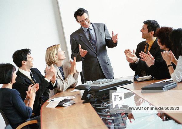 Geschäftsleute im Konferenzraum  applaudierender stehender Geschäftsmann