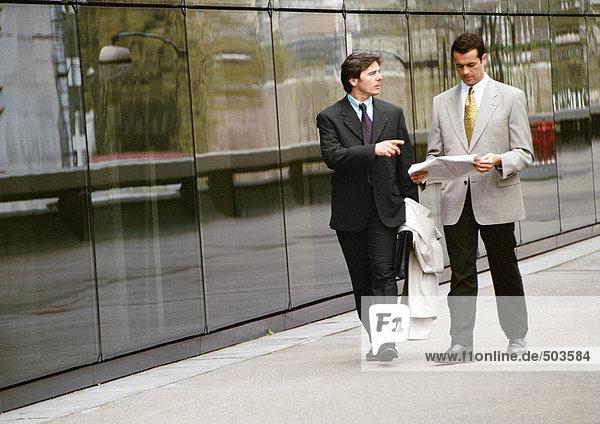 Zwei Geschäftsleute  die den Bürgersteig vor dem Gebäude entlanggehen.